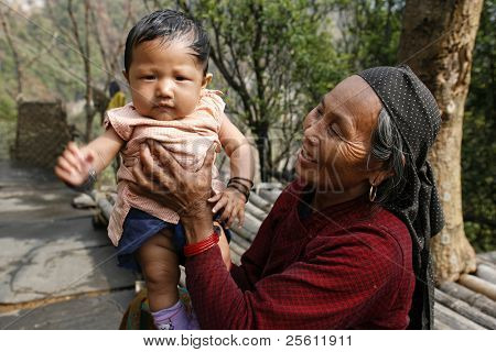 gurung grand mother with grandchild, annapurna, nepal