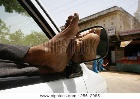 lazy taxi driver with feet up in car, Pushkar, India