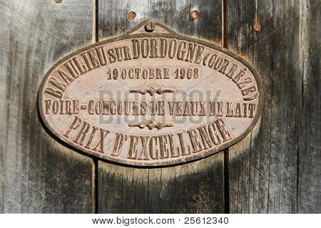 Preis-Medaille vom Vieh-Wettbewerb hing an Scheunentor in Correze, Frankreich