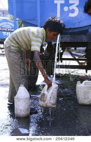 DELHI, INDIA - SEPTEMBER 22 : A young boy collects drinking water during water shortage on September 22, 2007 in Delhi, India. Delhi is the second most populous city in India.