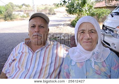 OLYMPOS, TURKEY -  AUGUST 3: Portrait of old Turkish couple sells produce on road side in Olympos, Turkey on August 3, 2007. Olympos is located 90 km southwest of Antalya city near Kemer.