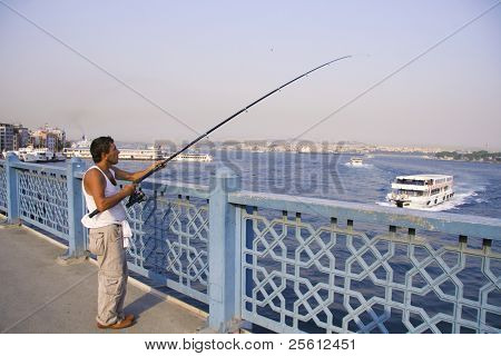 ISTANBUL - JULY 25 : A local fisherman fishing on a bridge in Istanbul, Turkey on July 25, 2007. Istanbul generates 21.2% of Turkey's gross national product.