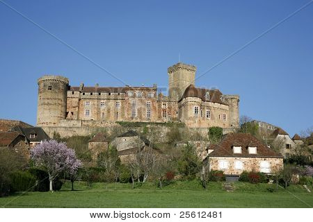 Castle and old village of Bretenoux in green fields, France