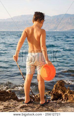 Young boy fishing with bucket on rocks on the island of Brac, Croatia