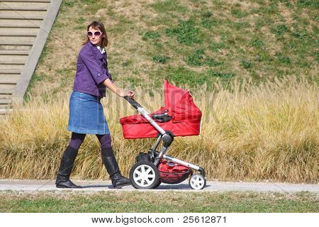Young mother pushing pram in park on sunny day