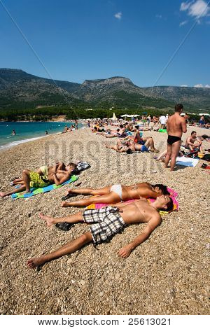 ZAGREB - JULY 29: Crowded beach of Zlatni Rat on June 05, 2009 in Bol Croatia. Bol is one of the busiest tourist desinations on the adriatic islands.