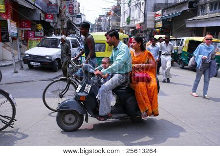 DELHI - SEPTEMBER 19: Mother, father and small child riding on scooter through busy city street on September 19, 2007 in Delhi, India. Up to six family members manage to ride these  two wheelers.
