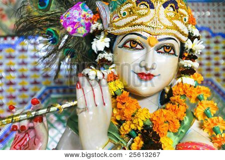 Statue of garlanded Hindu god Krishna playing flute in Delhi, India.