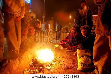 DELHI - JANUARY 18: Crowd of day workers wait around street fire in early morning on January 18, 2008 in Delhi, India. These men are not paid more than 2 dollars a day.