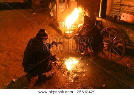 DELHI - 18 de JAN: Multitud de día trabajadores esperan alrededor del fuego de calle en la madrugada en 18 de enero de 2008 en