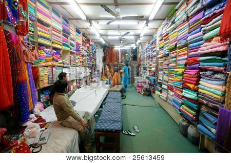 DELHI - JAN 19: Ladies choosing fabric for saris in textile shop on January 19, 2008 in Delhi, India. Saris can range from four to nine metres in length.