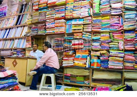 DELHI - DECEMBER 2: Two textile merchants sit in a wholesale shop stacked with fabric on shelves on December 2, 2007 in Delhi, India. Textiles exports may touch $24 billion in 2010-11