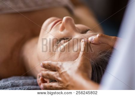 poster of Closeup face of mature woman having facial massage at spa. Senior woman lying at spa while a massage