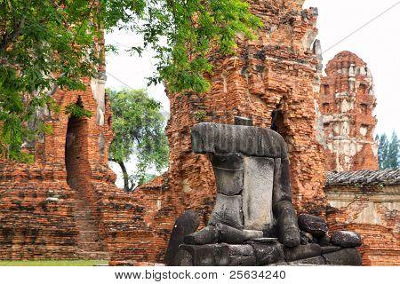 headless und armlose Buddhafigur sitzt vor Pagode in Ayutthaya, thailand