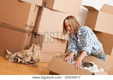 Moving house: Happy woman unpacking box in new home, kitchen, pots and pans