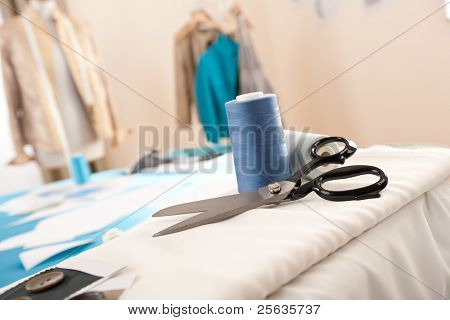 Fashion designer studio with professional equipment, sketches, mannequin, cloth