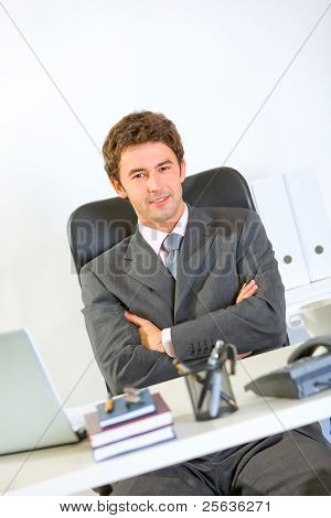 Portrait Of Modern Businessman Sitting At Office Desk