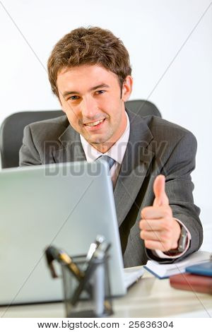 Modern Businessman Working On Laptop And Showing Thumbs Up