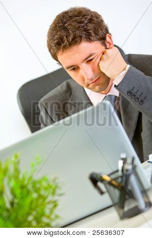 Bored Modern Businessman Working On Laptop At Office