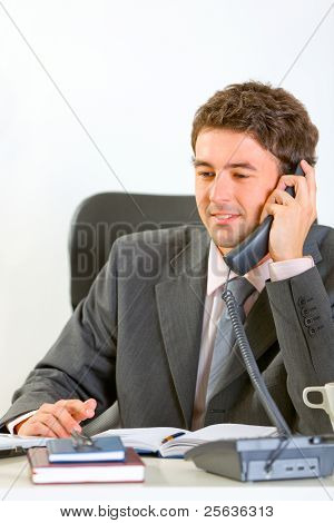 Modern Businessman Sitting At Office And Speaking Phone
