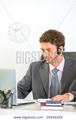 Lächelnd modernen Geschäftsmann mit Headset suchen In Laptop