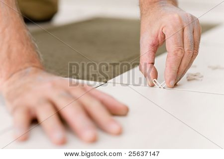 Home improvement, - close-up of handyman placing tile spacer