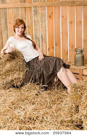 Young romantic woman with glass of natural milk in barn