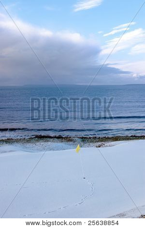 Golf Hole In Ireland In Winter Weather With Yellow Flag