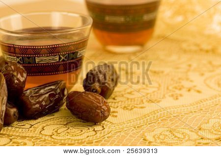 Ripped dates and a cup of tea placed on a golden matt.