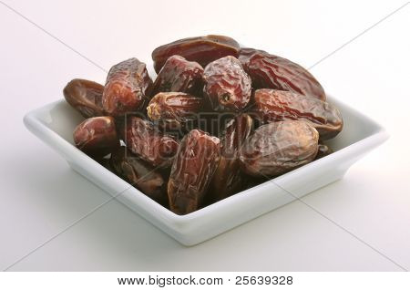 Plenty of dates arranged in a white bowl