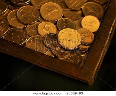 An UAE one Dirham coin in a wooden box