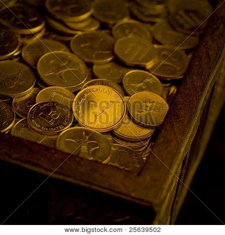 A heap of UAE Dirham coins in a trunk.