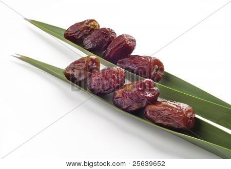 Ripped dates arranged on a palm tree laves