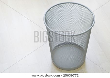 An empty waste-bin on wooden floor