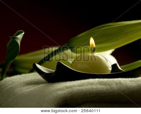A candle on a towel at spa
