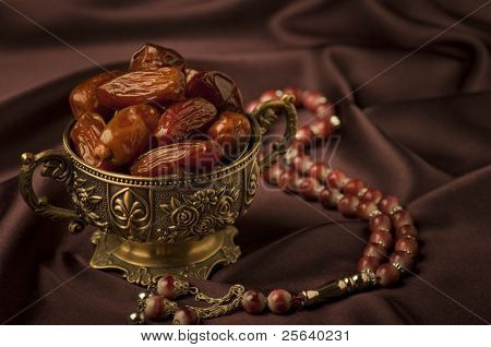 A bowl of dates and an Islamic rosary on velvet background