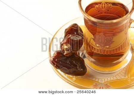 A close up of a cup of arabic tea and dates