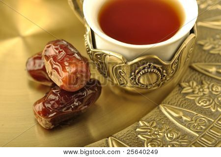 A royal, golden cup of tea with dates