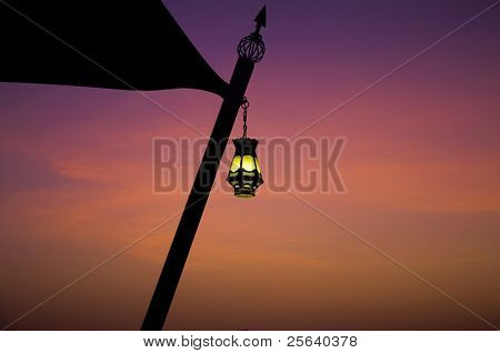 A hanging arabic lamp against a serene sky