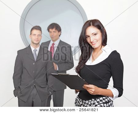 Businesswoman smiling with colleague in the background