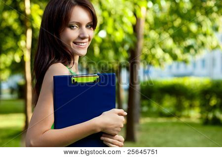 brunette woman holding blue tablet
