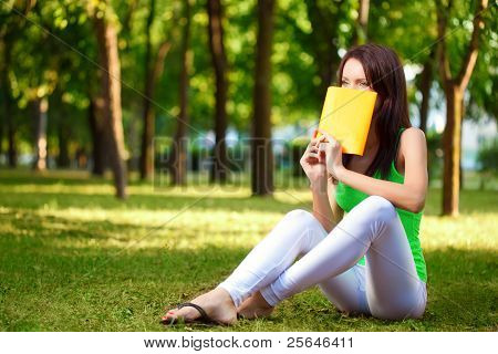 woman cover the face with book at park