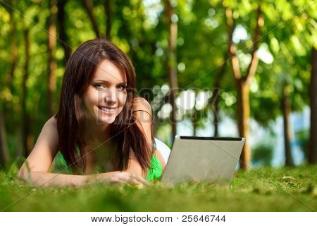 woman laying on grass with laptop