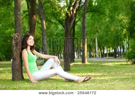 brunette woman sitting under the tree