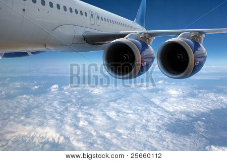 Big airliner in the blue sky with clouds.