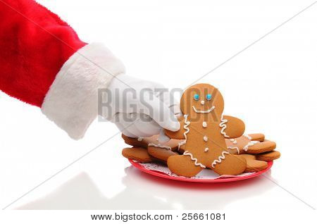 Santa Claus arm reaching to take a gingerbread man cookie from plate. Horizontal format over a white background with reflection - showing only hand and sleeve..