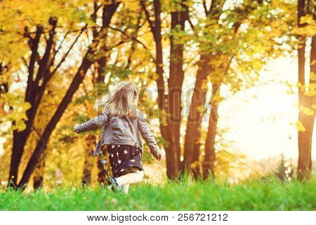poster of Happy Child Girl Running In Autumn Park. Little Girl Having Fun In Autumn. Happy Childhood. Stylish