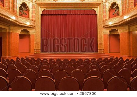 Cinema Stage With Red Velvet Curtains And Empty Chairs