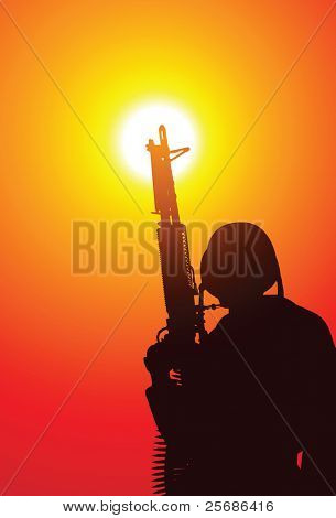 Soldado con una ametralladora en puesta de sol