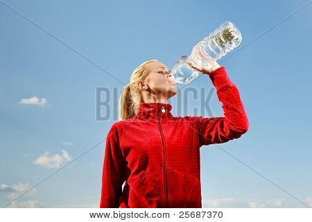 Young Woman Drinking Water From Plastic Bottle